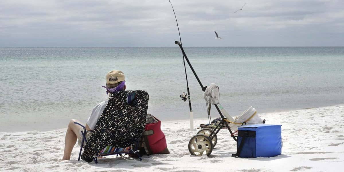 Relaxed mature woman fishing in the Gulf of Mexico, looking out to sea.